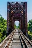 Opinião de desaparecimento do ponto de um cavalete velho da estrada de ferro com uma ponte de fardo velha do ferro sobre o Rio Br Imagem de Stock