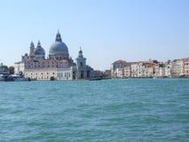 Opinião de dia de verão da água à lagoa Venetian com a basílica de Santa Maria della Salute em Veneza, Itália foto de stock