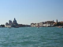 Opinião de dia de verão da água à lagoa Venetian com a basílica de Santa Maria della Salute em Veneza, Itália imagem de stock royalty free