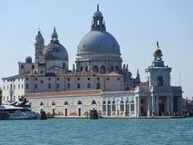 Opinião de dia de verão da água à lagoa Venetian com a basílica de Santa Maria della Salute em Veneza, Itália imagem de stock