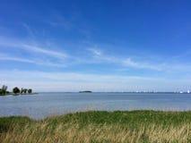 Opinião de IJsselmeer com barcos e ilha Fotografia de Stock Royalty Free