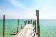 Opinião de perspectiva da ponte de madeira velha que estende no mar imagens de stock