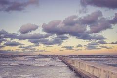 Opinião de perspectiva de um cais concreto no mar no por do sol Foto de Stock