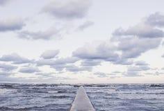 Opinião de perspectiva de um cais concreto no mar no por do sol Imagens de Stock