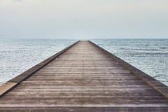 Opinião de perspectiva de um cais de madeira no mar tropical Fotos de Stock Royalty Free