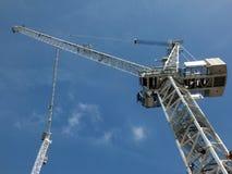 Opinião de perspectiva de dois guindastes de construção brancos altos em um terreno de construção contra um céu azul com nuvens fotos de stock