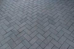 Opinião de perspectiva Gray Brick Stone Pavement monótonos na terra para a estrada da rua Passeio, entrada de automóveis, Pavers, fotografia de stock