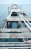 Opinião de perspectiva de um cais de madeira oxidado velho no beira-mar com mar azul Foto de Stock Royalty Free
