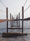 Opinião de perspectiva de um molhe oxidado quebrado abandonado do ferro que corre ao mar foto de stock