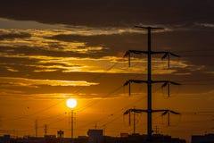 Opinião de polos elétricos de alta tensão, por do sol fantástico da silhueta como o fundo fotografia de stock royalty free