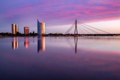 Opinião de Riga na ponte cabo-apoiada sobre o rio do Daugava e em construções novas no outro banco dele Fotos de Stock
