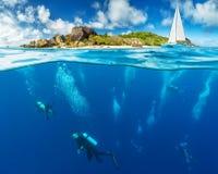 Opinião de superfície inferior e à superfície da àgua os mergulhadores fotografia de stock royalty free