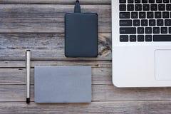Opinião de tampo da mesa de um portátil, de um disco rígido externo, de um caderno e de uma pena, Fotografia de Stock Royalty Free