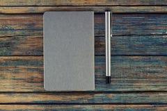 Opinião de tampo da mesa do caderno e de uma pena Fotos de Stock