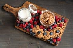Opinião de tampo da mesa dos frutos da floresta e das cookies caseiros colocados na placa de madeira imagem de stock