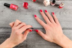 Opinião de tampo da mesa nas mãos da jovem mulher, aplicando o segundo revestimento do vermelho imagem de stock