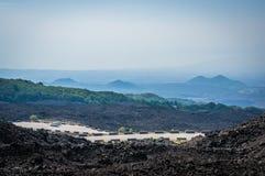 A opinião de Volcano Etna com os turistas em seus carros e lava apedreja tudo ao redor na névoa foto de stock