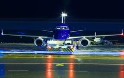Opinião detalhada alta do close up no avião bimotor azul moderno do passageiro que taxiing na noite pelo caminhão de reboque em Imagens de Stock