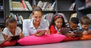 Opinião dianteira as crianças caucasianos do professor fêmea e da escola que estudam na tabuleta digital no schoo 4k filme