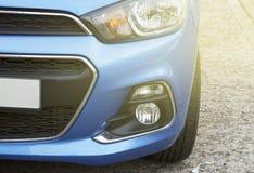 A opinião dianteira do carro desportivo azul, faróis close-up, tonificou imagem de stock royalty free