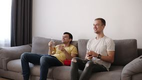 Opinião dianteira dois companheiros de quarto, amigos que olham o futebol na tevê que senta-se em um sofá confortável na sala de  filme