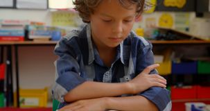 Opinião dianteira a estudante caucasiano que estuda na mesa na sala de aula na escola 4k vídeos de arquivo