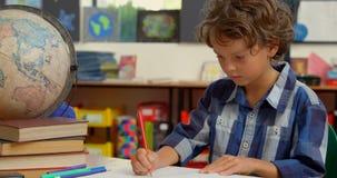 Opinião dianteira a estudante caucasiano que estuda na mesa na sala de aula na escola 4k filme