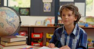 Opinião dianteira a estudante caucasiano que levanta a mão na mesa na sala de aula na escola 4k filme