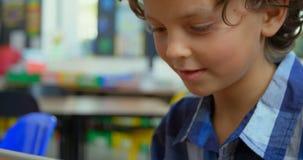Opinião dianteira a estudante caucasiano que usa a tabuleta digital na sala de aula na escola 4k filme