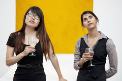 Opinião dianteira fêmeas novas com o vidro de vinho que olha acima na galeria de arte Fotografia de Stock