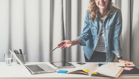 Opinião dianteira a jovem mulher que está no escritório do desenhista perto da tabela em que há catálogos, portátil, tablet pc imagem de stock