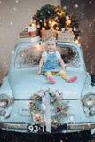 Opinião dianteira a menina bonito pequena doce e elegante que senta-se no carro retro azul decorado para o Natal fotografia de stock