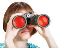 A opinião dianteira a menina olha através dos binóculos Foto de Stock
