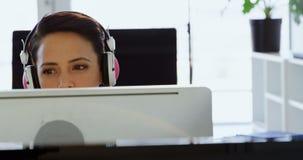 Opinião dianteira a mulher de negócios caucasiano nos fones de ouvido que trabalham no computador na mesa no escritório 4k filme