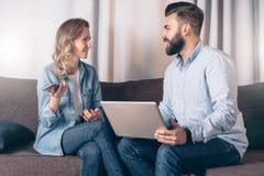 Opinião dianteira a mulher de negócios nova que senta-se no sofá na sala e que fala ao homem de negócios que senta-se na frente d Fotos de Stock