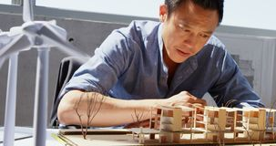 Opinião dianteira o arquiteto masculino asiático que olha o modelo arquitetónico em um escritório moderno 4k video estoque