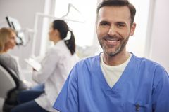 Opini?o dianteira o dentista masculino de sorriso na cl?nica do dentista fotografia de stock royalty free