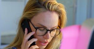 Opinião dianteira o desenhador de moda fêmea caucasiano que fala no telefone celular no escritório 4k filme