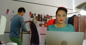 Opinião dianteira o desenhador de moda fêmea que trabalha no portátil na oficina 4k vídeos de arquivo