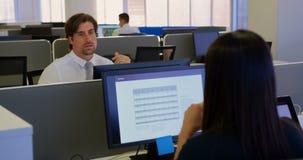 Opinião dianteira o executivo masculino caucasiano novo que fala com o executivo fêmea no escritório moderno 4k vídeos de arquivo