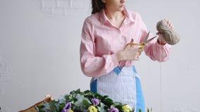 A opinião dianteira o florista corta uma linha com tesouras para arranjar um ramalhete fotografia de stock royalty free