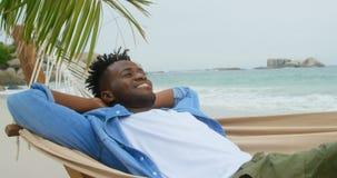 Opinião dianteira o homem afro-americano que relaxa em uma rede na praia 4k filme