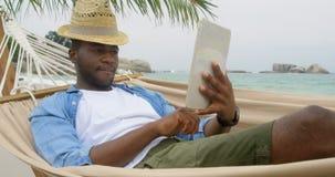Opinião dianteira o homem afro-americano que usa a tabuleta digital na praia 4k filme