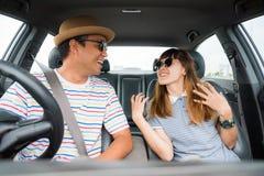 Opinião dianteira o homem asiático e a mulher dos pares engraçados do momento que sentam-se no carro Apreciando o conceito do cur fotos de stock