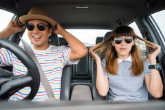 Opinião dianteira o homem asiático e a mulher dos pares engraçados do momento que sentam-se no carro Apreciando o conceito do cur fotografia de stock