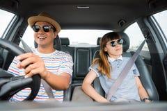 Opinião dianteira o homem asiático e a mulher dos pares engraçados do momento que sentam-se no carro Apreciando o conceito do cur imagens de stock royalty free