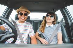 Opinião dianteira o homem asiático e a mulher dos pares engraçados do momento que sentam-se no carro Apreciando o conceito do cur foto de stock