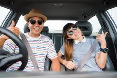 Opinião dianteira o homem asiático e a mulher dos pares engraçados do momento que sentam-se no carro Apreciando o conceito do cur imagem de stock