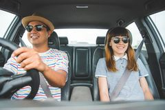 Opinião dianteira o homem asiático e a mulher dos pares engraçados do momento que sentam-se no carro Apreciando o conceito do cur fotografia de stock royalty free