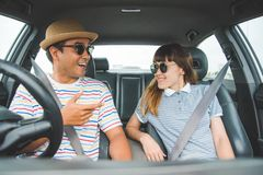 Opinião dianteira o homem asiático e a mulher dos pares engraçados do momento que sentam-se no carro Apreciando o conceito do cur fotos de stock royalty free